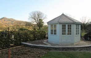 An attractive and traditional timber summerhouse with smooth shiplap cladding and a distinctive octagonal roof. The building has a slate composite roof and georgian windows that really finish the building off beautifully.