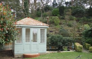 An attractive and elegant wooden summerhouse with cedar shingle roof and painted interior. The summerhouse has smooth shiplap cladding and is painted in the exterior shade of Lizard.