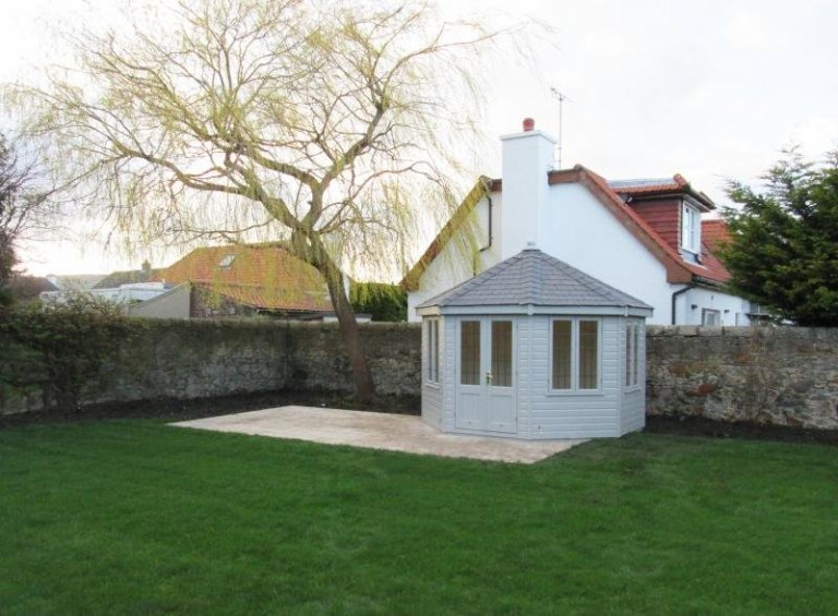 A large timber garden summerhouse with a distinctive octagonal roof and leaded glass. The wooden summerhouse has double doors and a hipped roof covered with grey slate composite tiles.