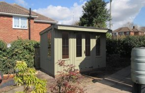 A charming timber national trust summerhouse with pent roof covered in a corrugated material. The national trust summerhouse has leaded windows and cast iron door furniture with vertical cladding and rustic cut timber.