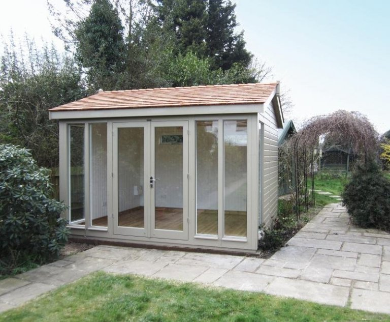 An attractive and traditional wooden garden studio with insulation and painted pine interior. The luxury garden room has an apex roof covered with cedar shingles and floor-to-ceiling windows.
