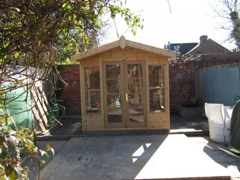 A chalet-style wooden summerhouse with an apex roof and double doors. The traditional wooden summerhouse is coated in light oak preservative.