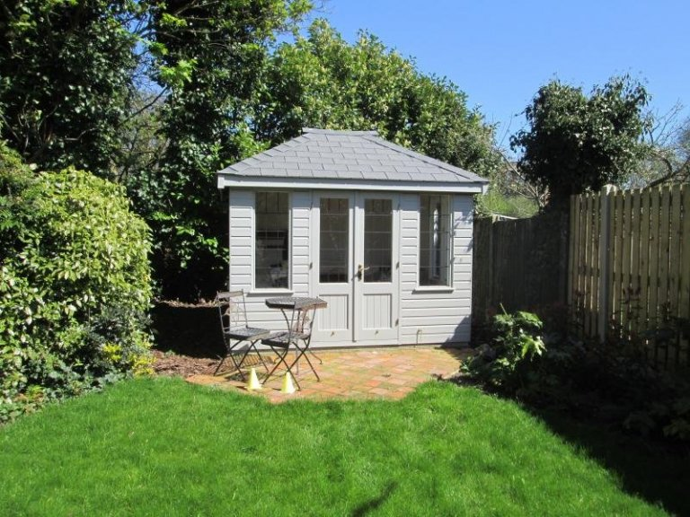 A stunning timber summerhouse nestled into the bottom of a customers garden. It has a hipped roof covered with grey slate composite tiles and has leaded windows.