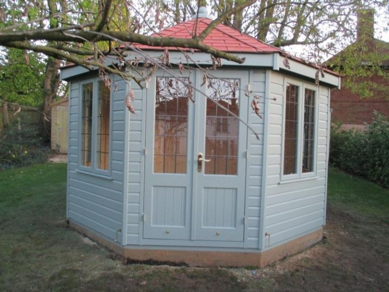 A wooden summerhouse with leaded windows and a distinctive octagonal shape. The wooden building is clad with smooth shiplap and painted in the exterior shade of verdigris.