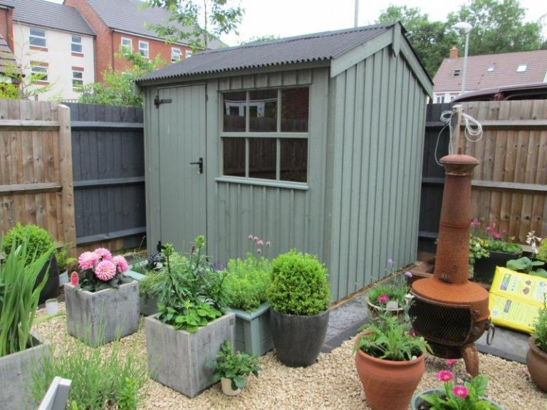 A traditional timber garden shed from our national trust range of sheds and summerhouses. The wooden garden shed boasts georgian windows and vertical cladding painted in the national trust paint shade of terrace green.