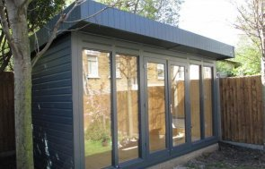 modern and contemporary garden studio with floor to ceiling windows and electrics. The wooden garden room has been painted in the exterior shade of slate