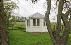 A traditional wooden summerhouse painted in ivory with smooth shiplap exterior and leaded windows. The timber building has a roof covered in slate composite tiles and has both insulation and electrics.