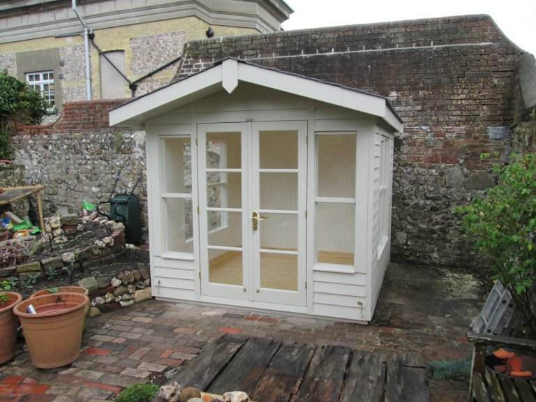 Insulated and lined summerhouse with apex roof and chalet-style double doors. The wooden garden summerhouse boasts rustic weatherboard cladding and internal lacquered flooring.