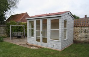 An attractive holkham summerhouse with insulation and a painted interior. The summerhouse has red slate composite tiles covering the roof and a shiplap clad exterior.