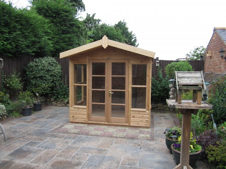 Blakeney Summerhouse with light oak preservative and a distinctive traditional style. The chalet-style summerhouse boasts double doors and windows and has an apex roof covered in heavy-duty felt.