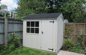 An attractive and traditional rustic garden shed from the national trust range of sheds and summerhouses. The building has vertical cladding and a georgian window. The shed has a corrugated roof and cast iron door furniture.