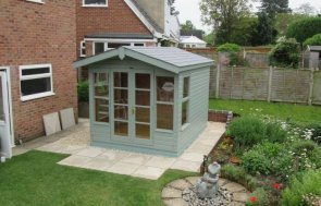 A high quality timber summerhouse with storage area. The stylish wooden summerhouse has a chalet appearance with double doors and a small roof overhang. It is clad with smooth shiplap and painted in the tasteful exterior shade of lizard.