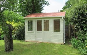 An attractive timber garden studio perfect for a work from home office. The garden studio has an apex roof and leaded windows with shiplap cladding painted in the light shade of sandstone.