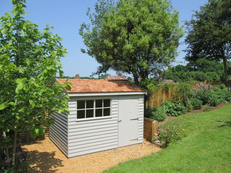 A rustic garden shed with weatherboard cladding and an apex roof covered in cedar shingles. The high quality timber garden shed is a spacious workshop with two georgian windows and traditional weatherboard cladding.