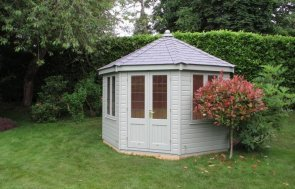 A traditional and attractive summerhouse with leaded windows and a grey slate tiled roof. The exterior of the summerhouse is clad with smooth shiplap and painted in the shade of pebble.