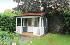 An attractive garden room with veranda and double door entry. It has an apex roof covered in cedar shingles and guttering added to the fascia boards. The timber garden room is insulated and lined with electrics and opening windows.