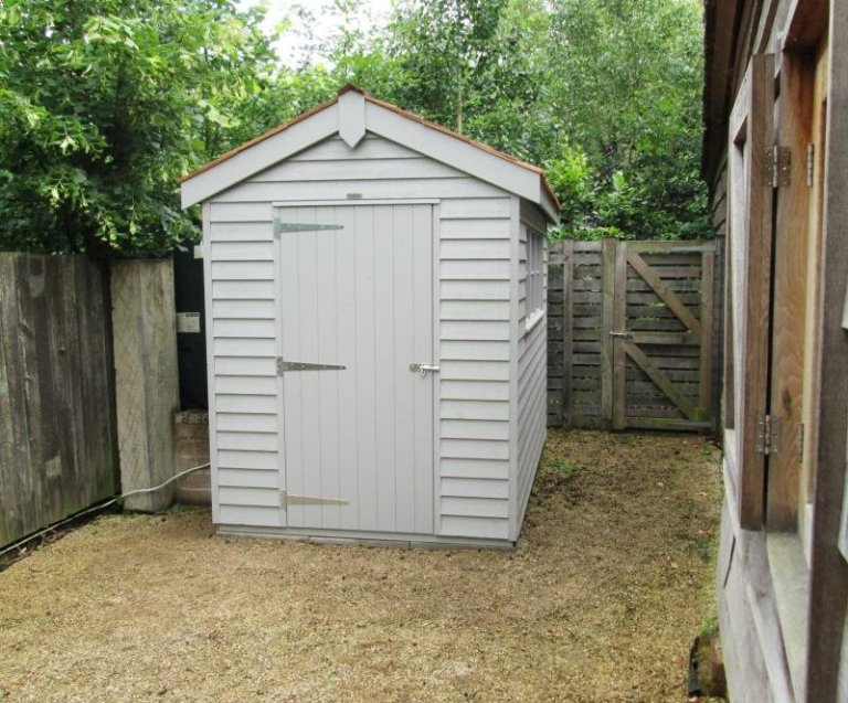 A superior garden shed with rustic weatherboard cladding and cedar shingle roof. The building has two windows in the length and is painted in the exterior opaque shade of Pebble.