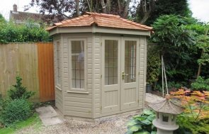 A small timber summerhouse with octagonal shape and cedar shingle roof. The wooden garden building has several opening leaded windows and a smooth shiplap exterior painted in the opaque paint shade of Taupe.