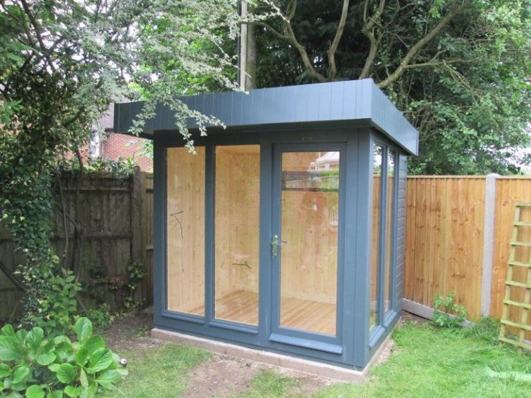 A fully insulated garden studio with natural internal pine matchboard and a pent roof. It is a modern contemporary garden building with floor-to-ceiling windows and an opening fanlight window for ventilation. The exterior is painted in the shade of Slate.