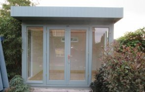 A stylish and contemporary wooden garden studio with a pent roof and floor-to-ceiling windows. The building boats internal insulation and lining and a smooth shiplap exterior painted in the shade of Pebble.
