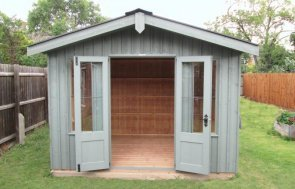 An attractive National Trust Summerhouse clad with vertically-sawn, rustic cut timber painted in our shade of Terrace Green. Selected from our range of National Trust sheds and summerhouses, the Ickworth summerhouse has corrugated roofing and cast iron door furniture.