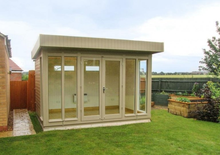 Attractive wooden garden studio. Modern timber garden studio office with floor to ceiling windows