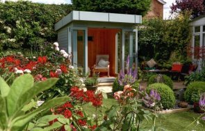 Modern garden studio with open front in a flower garden. The contemporary garden room has full length windows and a pent roof with a natural pine interior.