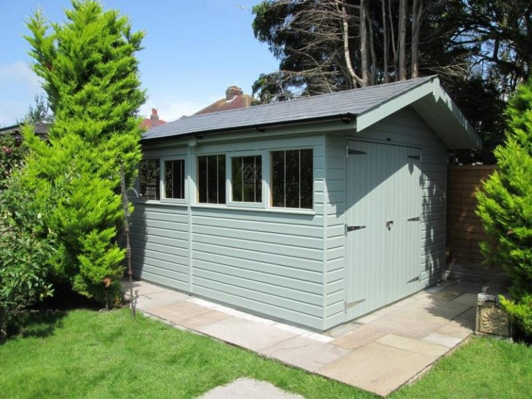 attractive garden shed with smooth shiplap cladding and a security pack. Timber garden shed with stainless steel windows. The shed has double doors and a small overhang on the gable end of the building.