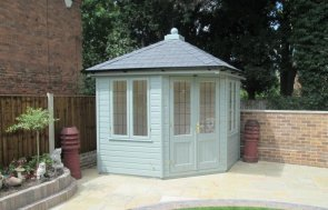 A timber corner summerhouse with hipped slate roof and leaded windows. The timber garden building has a shiplap exterior and black guttering. High quality summerhouse for corner gardens.