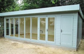 A large contemporary garden studio with fully glazed windows and smooth shiplap cladding. The timber garden building has a pent roof covered with heavy-duty felt and it is also a garden studio with electrics and heating.