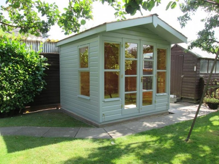 An apex chalet style summerhouse with double doors and a small overhang on the gable. The summerhouse has smooth shiplap cladding and is painted externally in the shade of lizard.