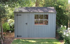 A charming national trust shed with vertically-sawn rustic cut cladding and a single georgian window. The apex roof is covered in a corrugated material and the building boasts cast iron door furniture.
