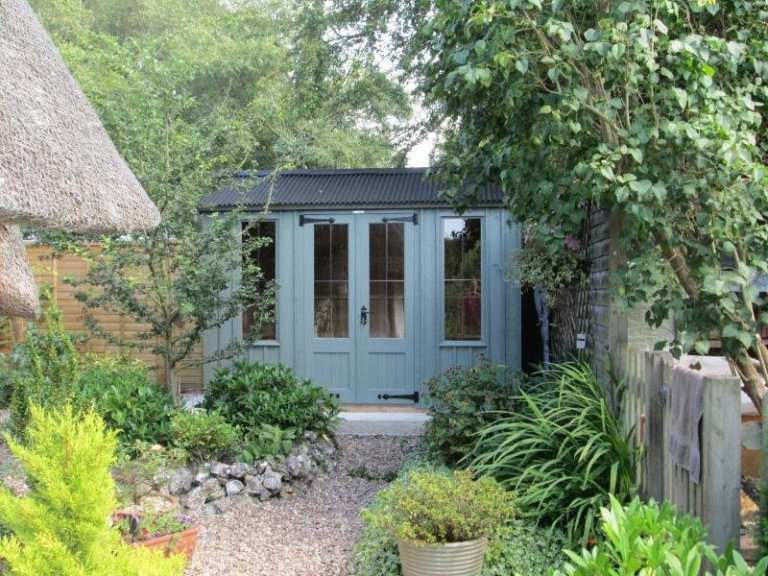 A traditonal summerhouse with apex corrugated roof and leaded windows. The Lavenham summerhouse has vertical cladding and cast iron door furniture.