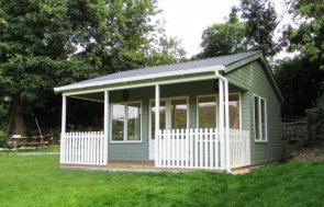 An attractive large wooden garden room with veranda. Timber garden building with overhanging roof and decking.