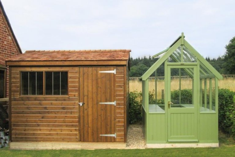 A superior timber shed and greenhouse beside each other. The shed has an apex roof covered in cedar shingles and a security pack with window bars while the greenhouse is a green colour with toughened safety glass.