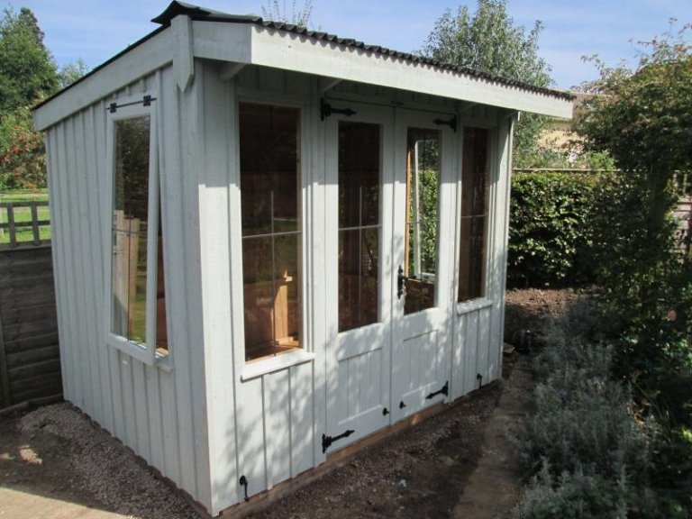 A rustic and traditional national trust summerhouse with a pent corrugated roof and leaded windows. Selected from our range of national trust sheds and summerhouses, the flatford timber summerhouse has cast iron door furniture and is painted in the national trust shade of painters grey.