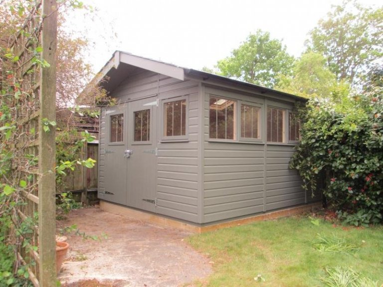 An attractive superior shed with apex roof and smooth shiplap cladding and black guttering. The building has a security pack added to it and is painted in Ash exterior paint. The apex roof has a small overhang and double doors.