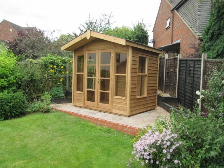 A chalet style summerhouse with double doors and a small overhang. The timber summerhouse is from our range of high quality sheds and summerhouses and boasts an apex covered felt roof.