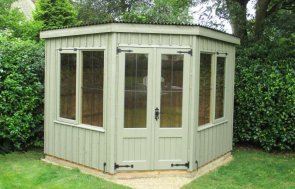 An attractive national trust corner summerhouse with vertically-sawn rustic cut cladding and leaded windows with cast iron door furniture and a pent roof covered with corrugated material.