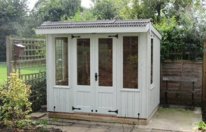 A charming and quaint National Trust summerhouse is from our range of national trust sheds and summerhouses and is painted in a light cream colour. It has a pent roof covered with corrugated material, leaded windows and double doors with cast iron furntiure.