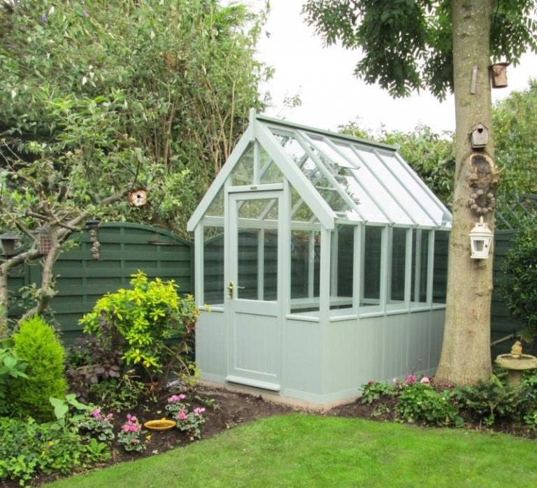 A traditional wooden greenhouse with toughened safety glass and automatic opening roof vents. The greenhouse has slatted workbenches and a smooth shiplap exterior painted in the exterior shade of lizard.