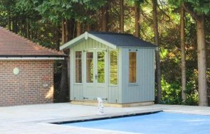 A traditional wooden summerhouse from the national trust range of sheds and summerhouses. The ickworth summerhouse has an apex roof with corrugated material and is painted in the shade of disraeli green with leaded windows and rustic cladding.