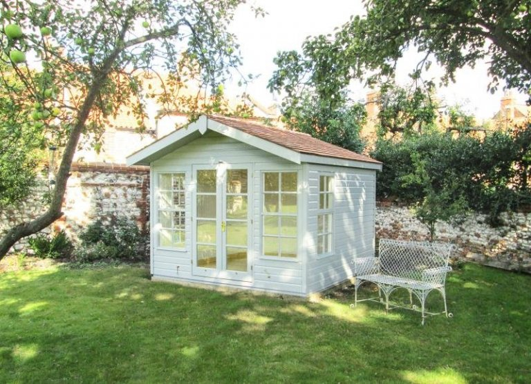 An attractive wooden painted summerhouse with double doors and large opening windows. The roof is covered with cedar shingles and the interior is painted. Charming traditional rustic summerhouse.