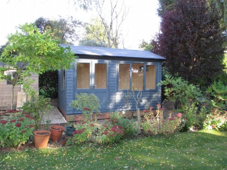 An attractive garden studio with desk height windows and a natural interior. Garden studio with a slate roof and insulation. Exterior painted in slate with rustic weatherboard cladding.