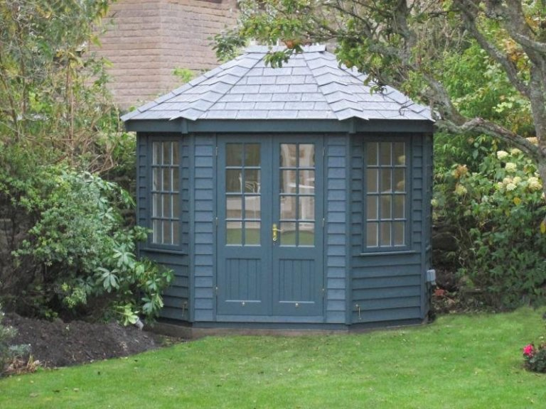 Charming octagonal summerhouse with a slate roof and rustic weatherboard cladding painted in the exterior shade of Slate. The building has traditional georgian windows and a painted interior.