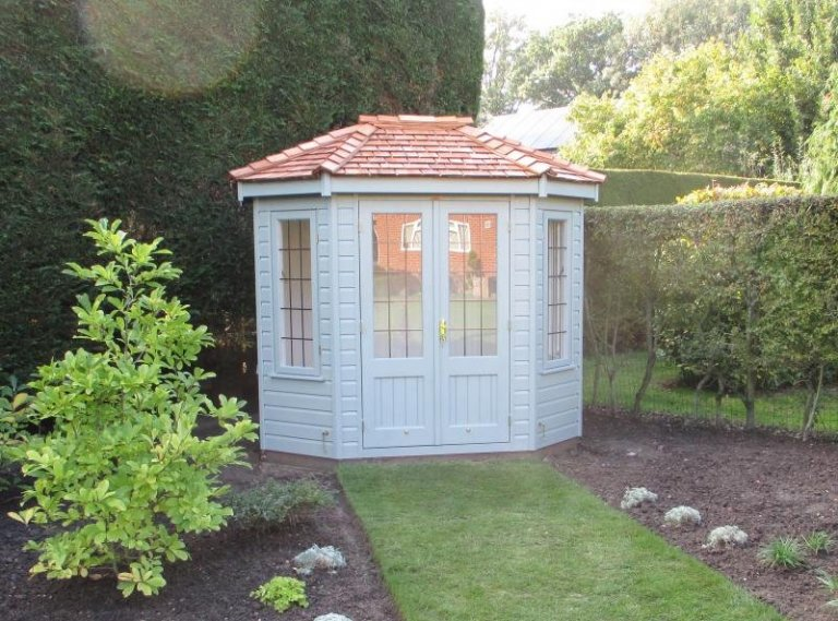 Small octagonal summerhouse with hipped cedar shingle roof and leaded windows. The interior of the summerhouse has insulation and lining painted in the airy shade of ivory.
