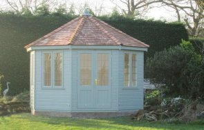 An octagonal summerhouse with leaded windows and a cedar shingle roof. The smooth shiplap exterior is painted in the contemporary shade of lizard.