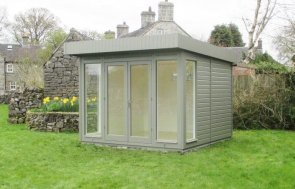 A contemporary and stylish garden studio with a pent roof and smooth shiplap exterior cladding painted in the exterior shade of ash. The building has several fully-glazed windows and a painted interior.
