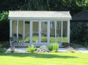 An attractive garden studio positioned in a well-kept garden with an apex roof covered in slate-composite tiles with eight fully-glazed windows.