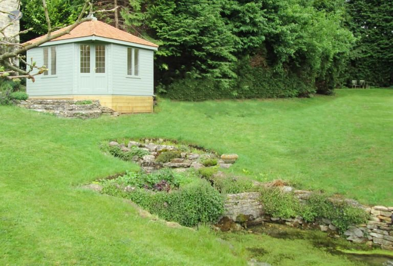 3.6 x 3.6m Weybourne Summerhouse painted in Exterior Lizard with leaded windows